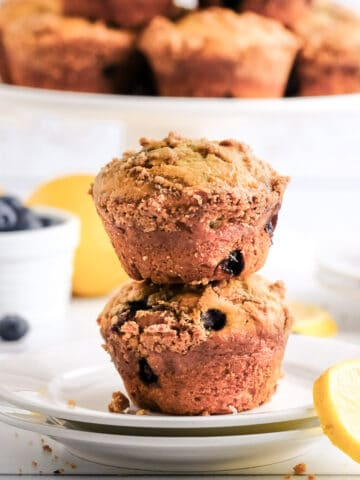 two blueberry lemon muffins on a white plate with a cake stand in the background and blueberries and lemon slices on the counter