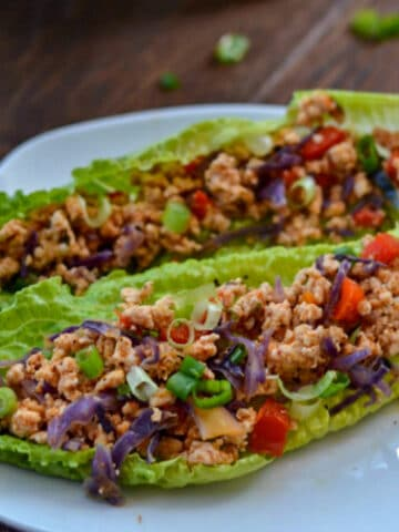 two lettuce wraps filled with ground turkey and red peppers