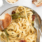 bowl of linguine noodles with asparagus and bacon pieces