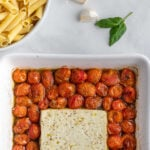 white square baking dish with cherry tomatoes surrounding a block of feta cheese