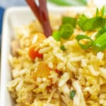 chicken fried rice in a white bowl with chopsticks
