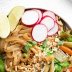 closeup of rice noodles toped with peanuts, radish slices, sliced carrots and green onions
