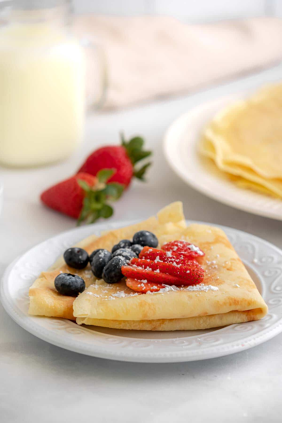 a white plate with two crepes folder and topped with blueberries, sliced strawberries and powdered sugar