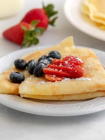 two homemade crepes folded and topped with blueberries and sliced strawberry