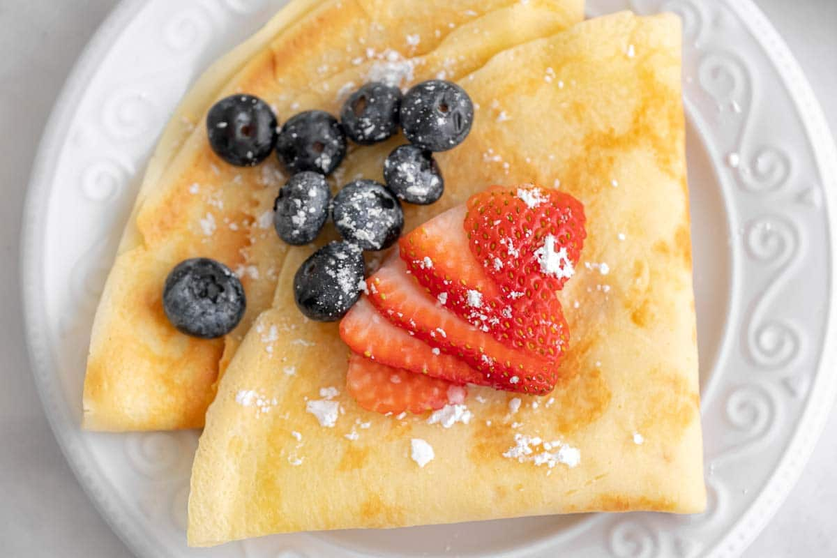 closeup of two folded crepes on a white plate topped with blueberries and strawberries