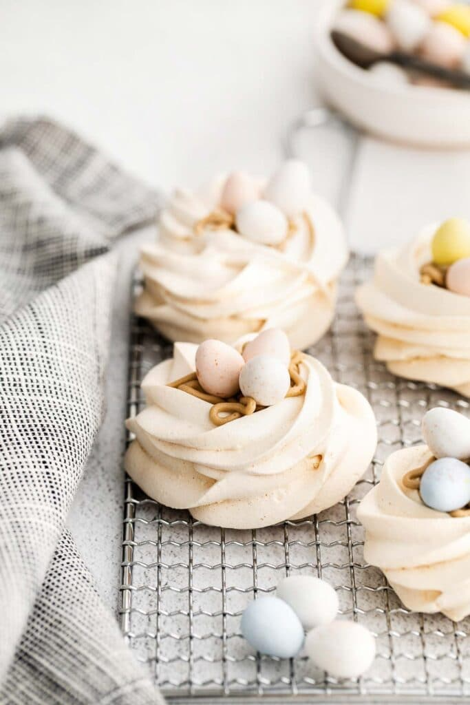 closeup of meringue nests on a wire rack with easter cadbury egg candy on top