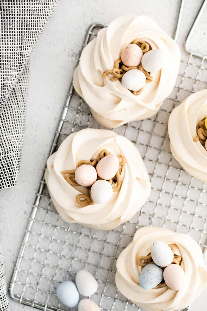 four meringue nests on a silver wire rack with eggs on top