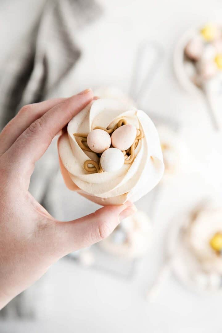 hand holding a meringue nest in fingers