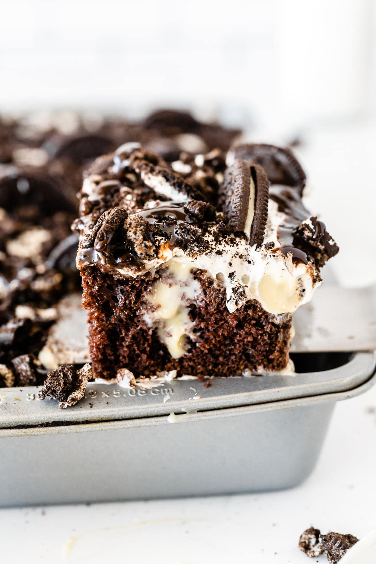 a slice of oreo poke cake being scooped on a spatula
