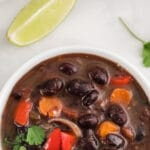 black bean soup in a white bowl with cilantro