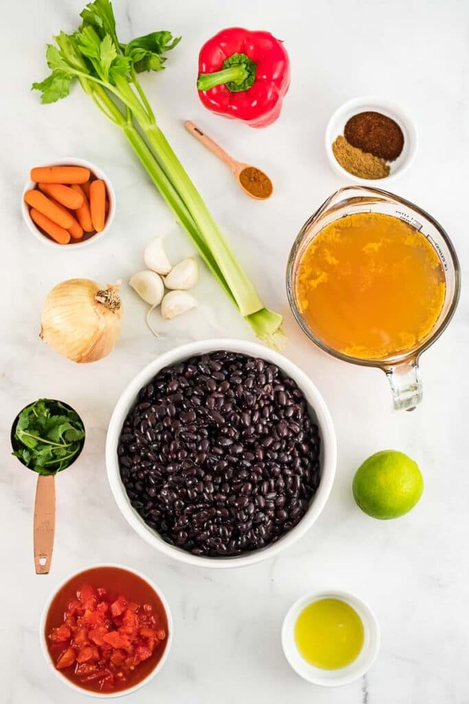 several ingredients for black bean soup in white bowls