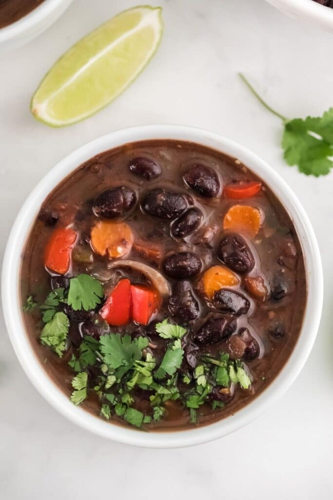 white bowl with black bean soup topped with cilantro