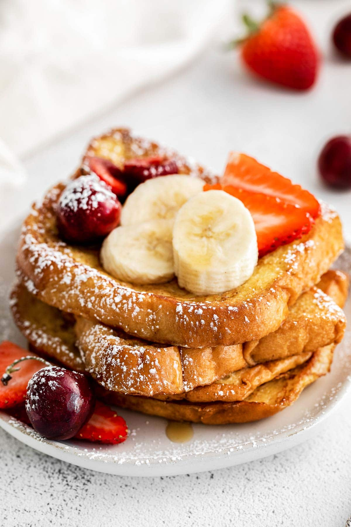 closeup of a stack of french toast topped with bananas, strawberries and powered sugar
