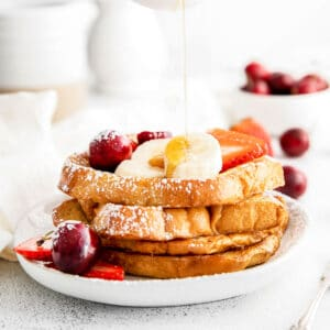 four slices of brioche french toast with slices of banana, cherries, strawberries and powdered sugar