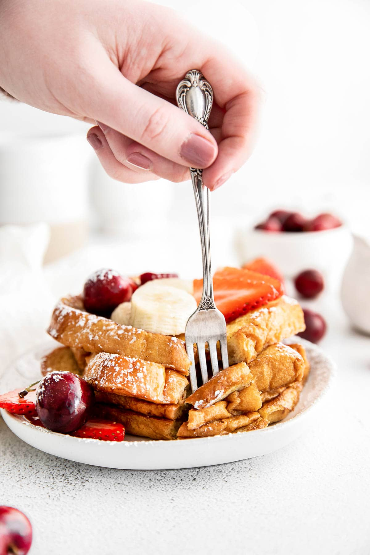 a stack of brioche french toast topped with sliced bananas, cherries and strawberries on a white plate with a fork