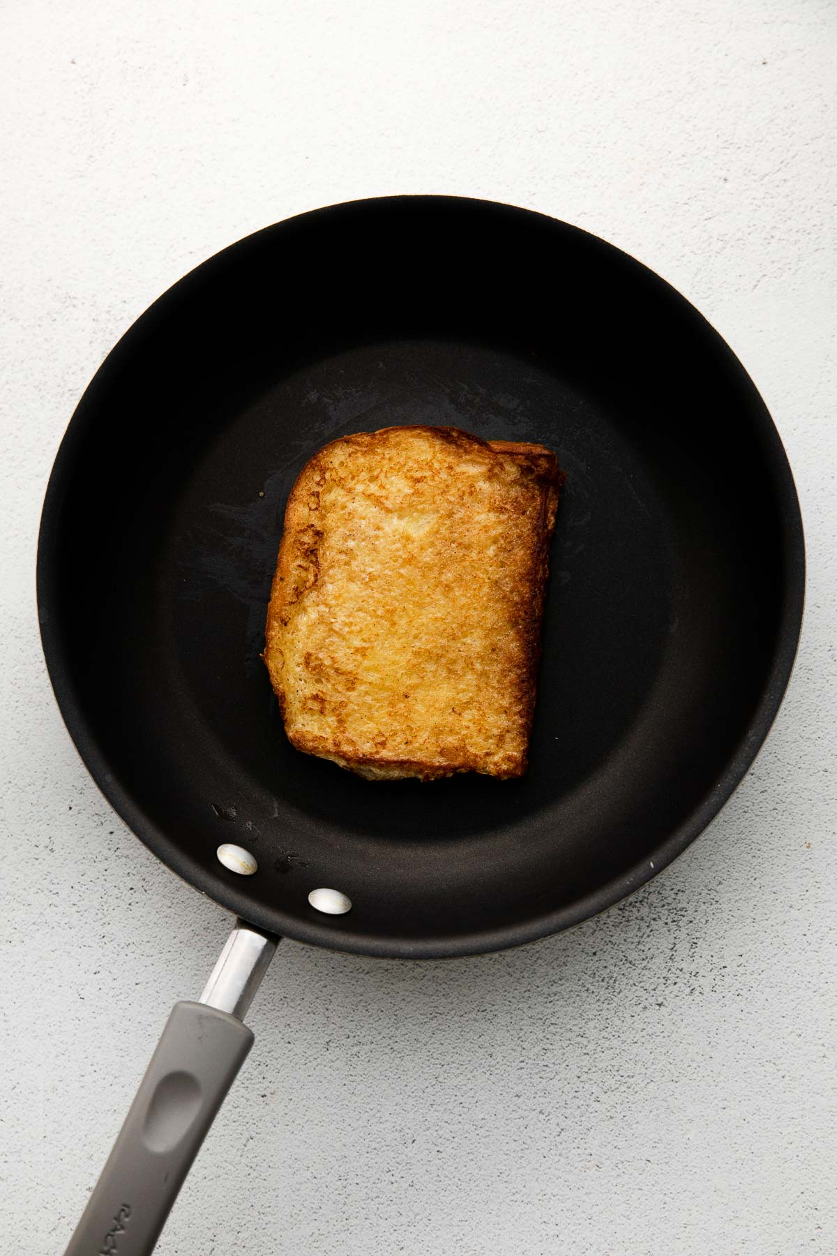 a black skillet with a slice of golden brown slice of brioche french toast