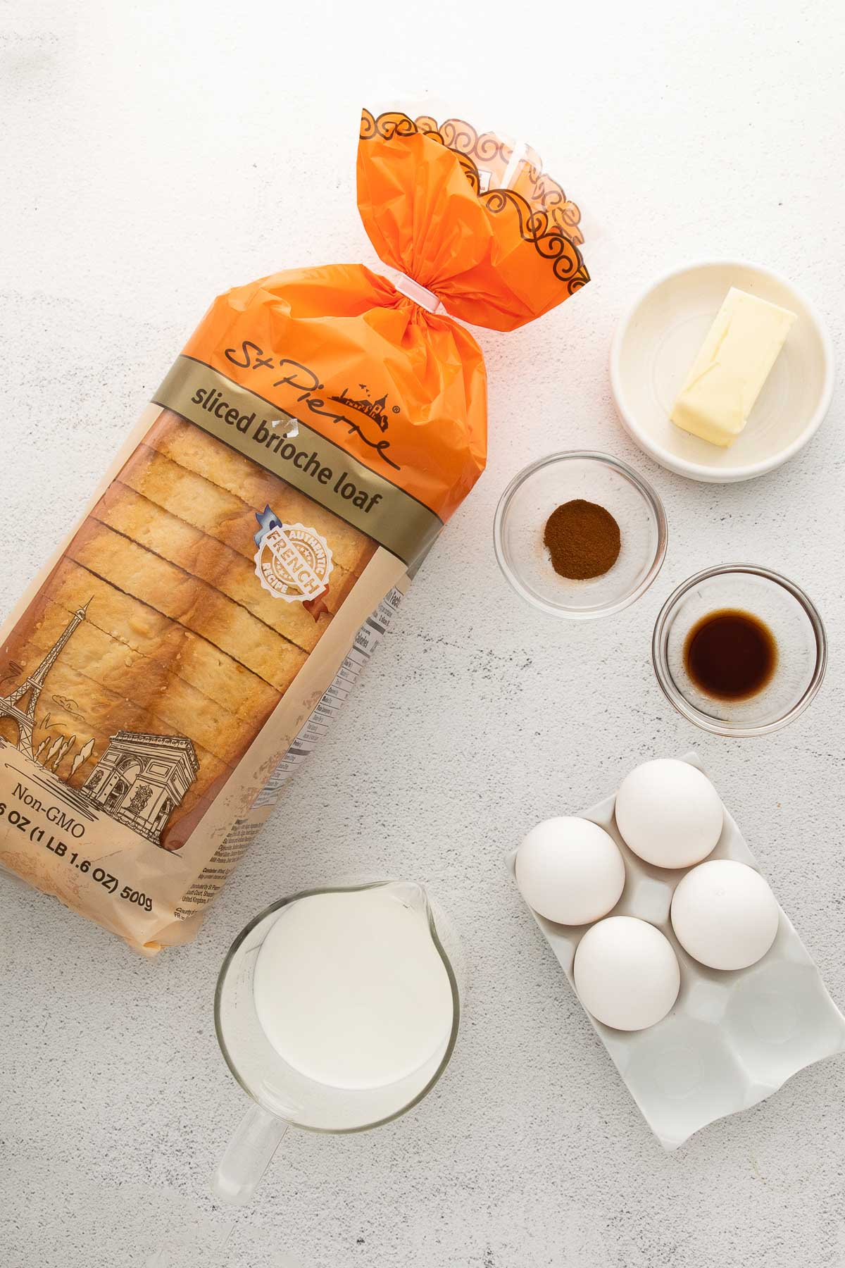 loaf of brioche bread, 4 eggs and bowls of milk, vanilla, cinnamon and butter
