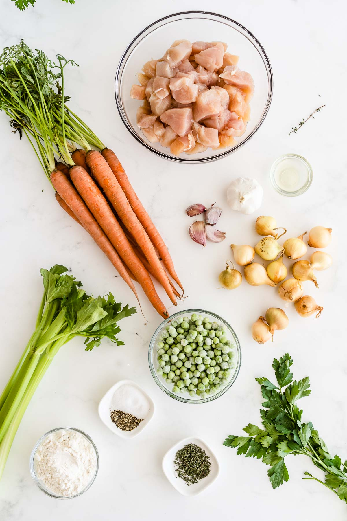 a glass bowl with raw chicken, whole carrots, celery stalks, garlic cloves, bowl of frozen peas