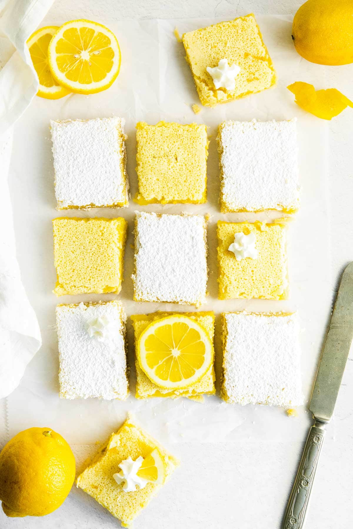 lemon bars on a white table cut into nine squares - some topped with powdered sugar and some topped with lemon slices