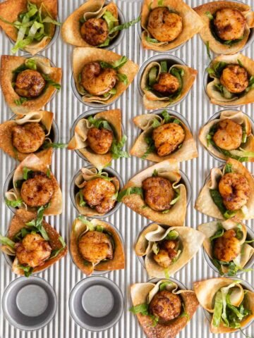 a mini muffin tin fulled with wonton wrapper cups and topped with shrimp