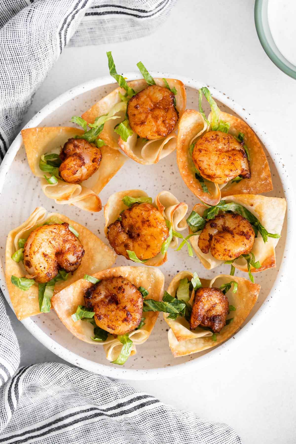 seven shrimp taco bites in a white round serving dish