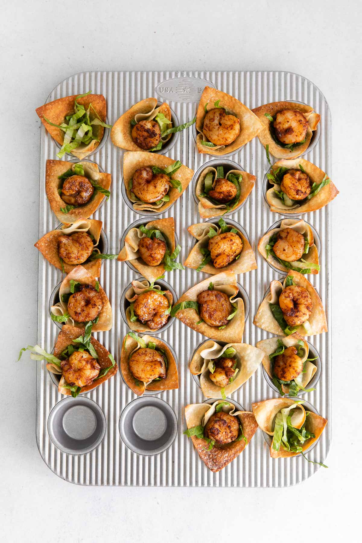 mini muffin tin filled with baked wonton wrappers each topped with shredded lettuce and a shrimp