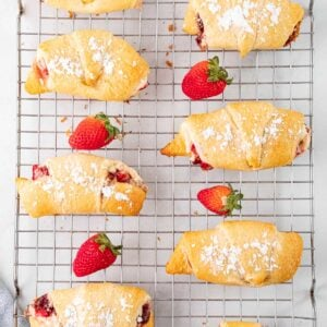 several crescent rolls on a wire cooling rack with fresh strwberries