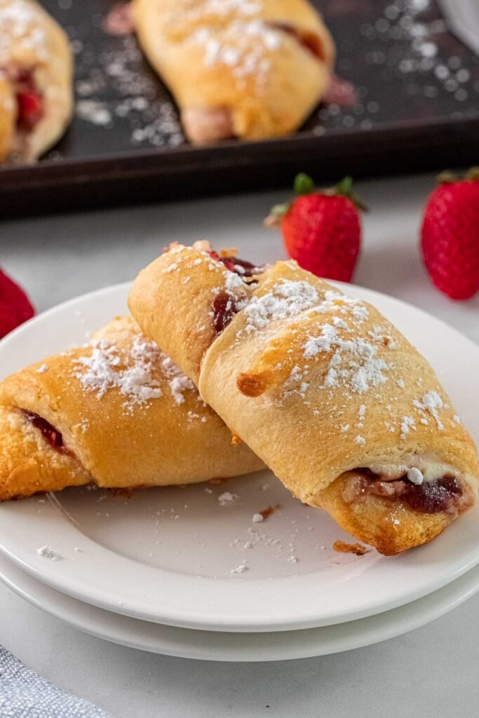 two crescent rolls topped with powdered sugar leaning on each other on a white plate
