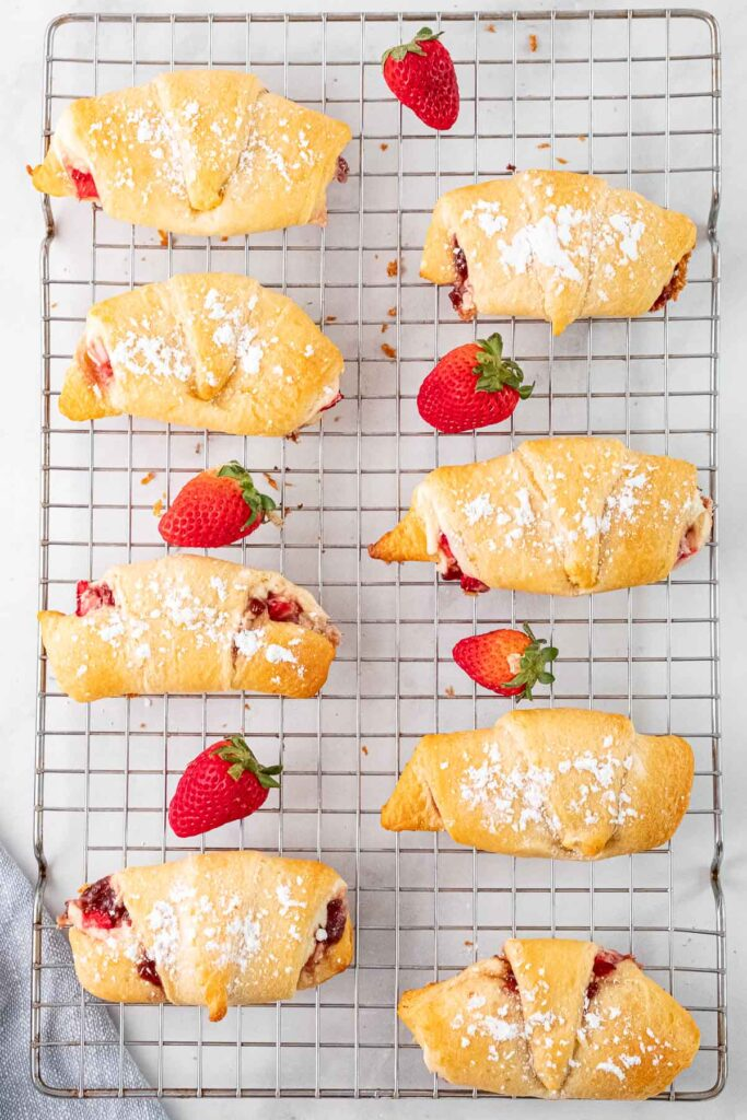 eight crescent rolls filled with strawberry cream cheese mixture and topped with powdered sugar on a wire rack