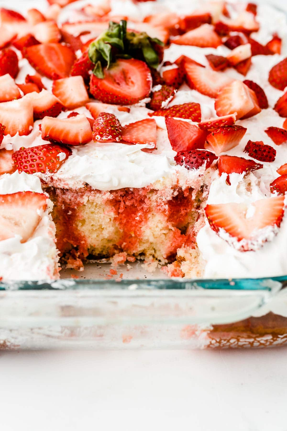 closeup of the inside of a strawberry and cream poke cake