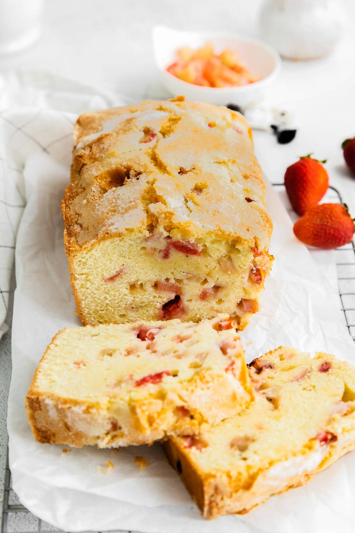 strawberry pound cake on a white parchment paper with two slices cut