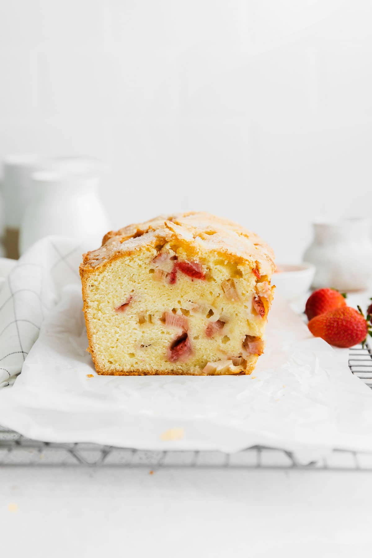 closeup of a cut strawberry rhubarb pound cake on a parchment paper lined wire rack