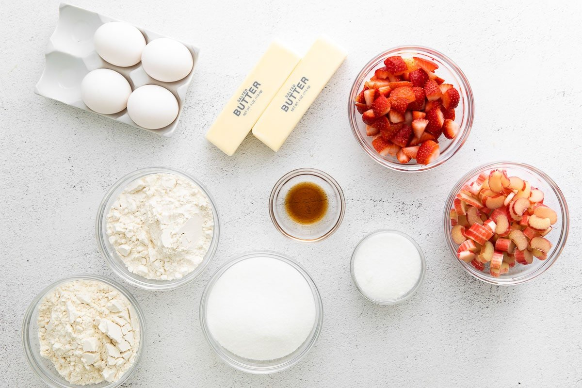 several bowls of flour, sugar, fresh strawberries and rhubarb, 2 sticks of butter and 4 eggs