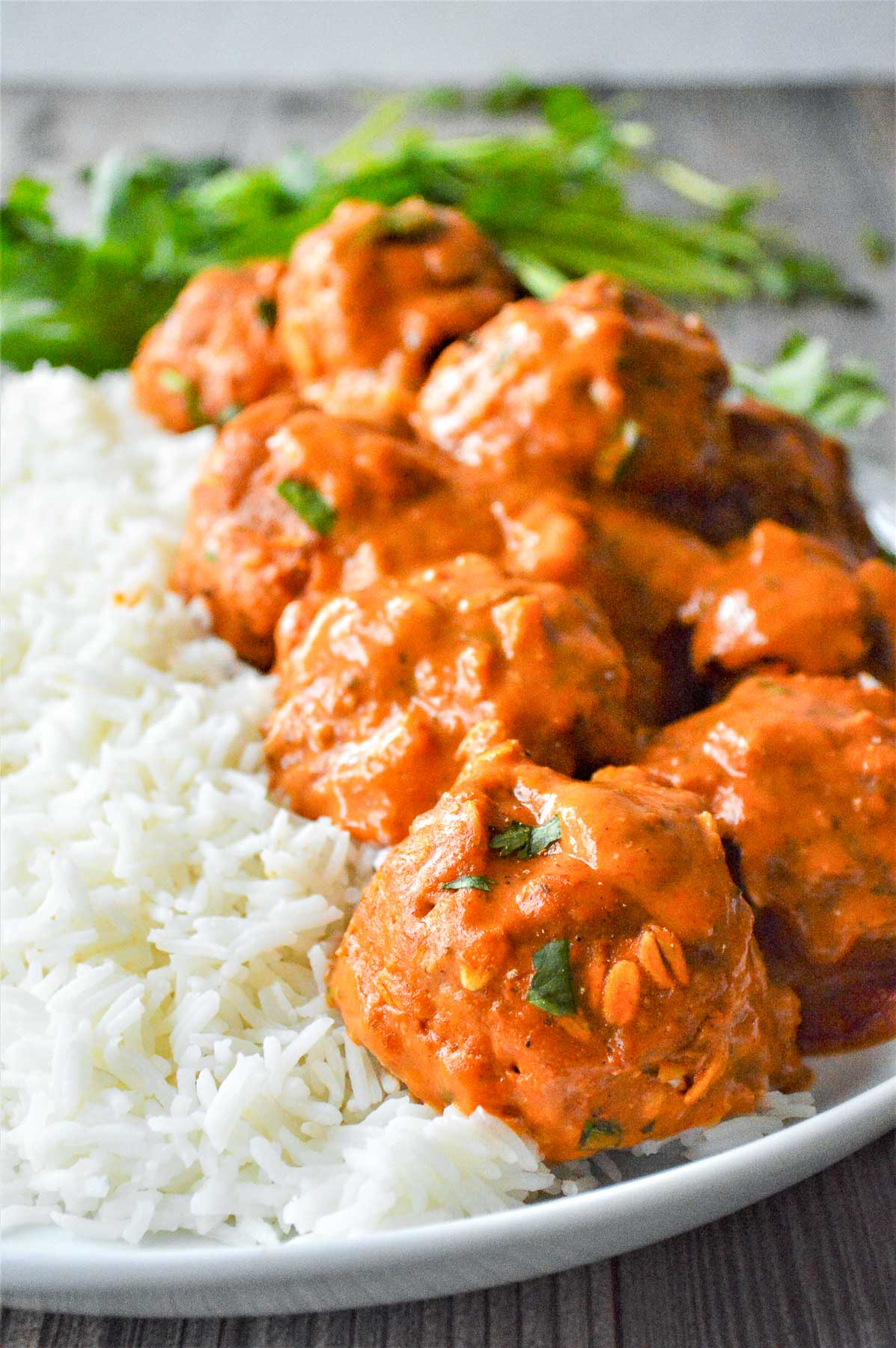 a white plate with several Tikka Masala Meatballs over white rice