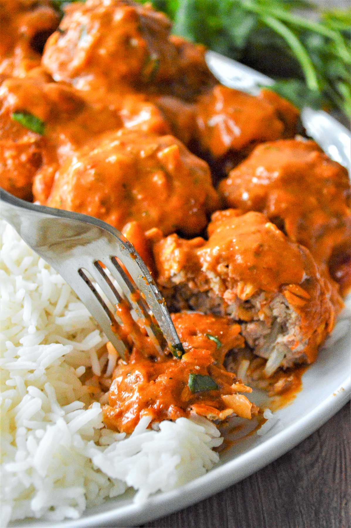 Tikka Masala Meatballs served on white rice being picked up with a fork