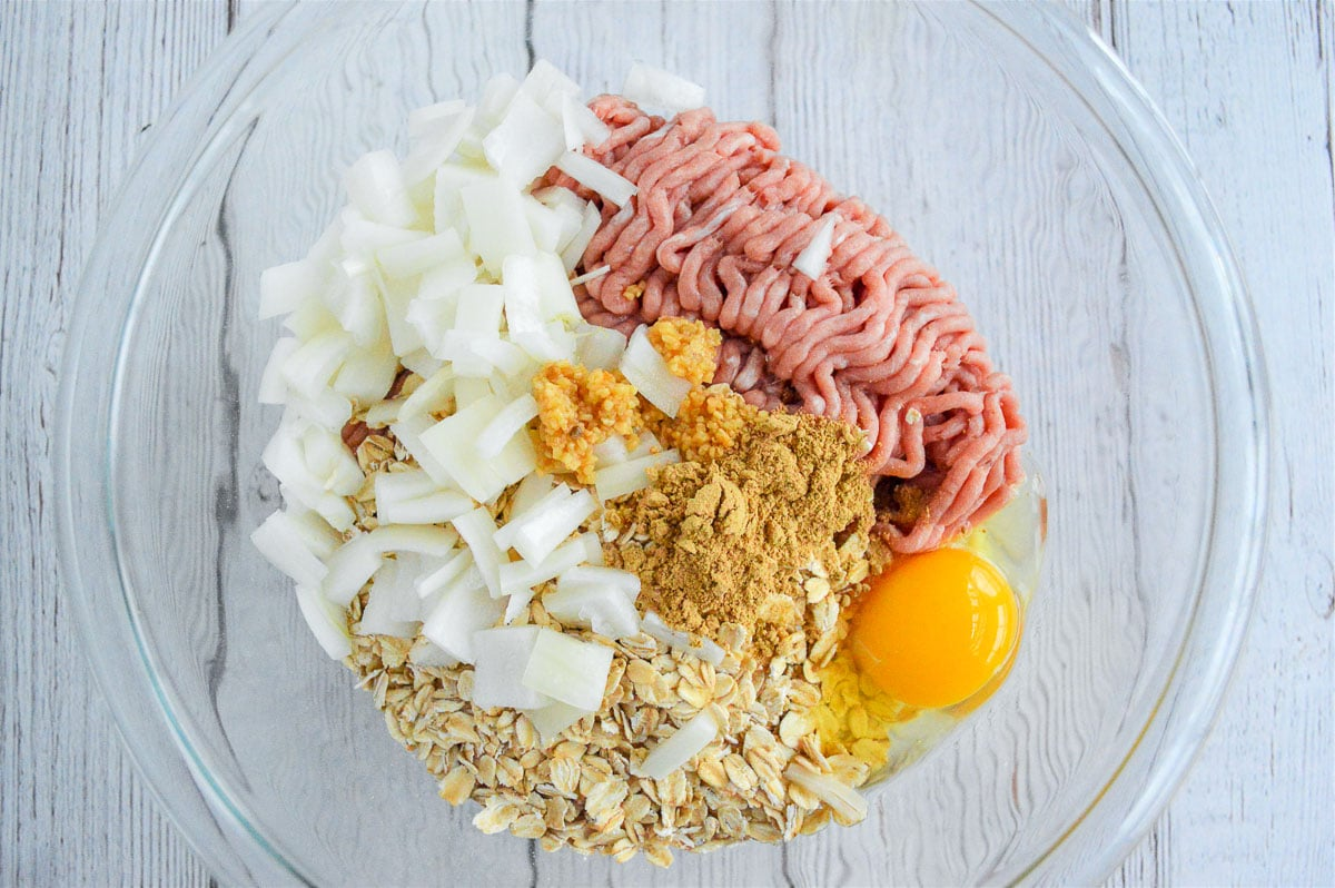 a glass bowl with raw ground turkey, oats, egg and garlic