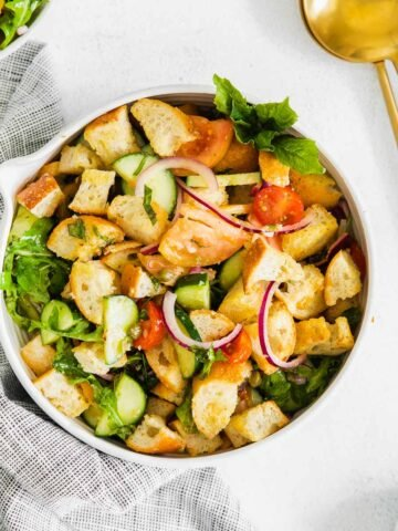 panzanella salad with arugula, bread cubes, tomatoes, red onions and cucumbers