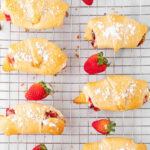eight crescent rolls filled with strawberry cream cheese mixture and topped with powdered sugar on a wire rack with text overlay