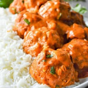 closeup of tikka masala meatballs over white rice