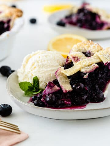 a slice of blueberry pie with lattice top with a scoop of vanilla ice cream on a white plate