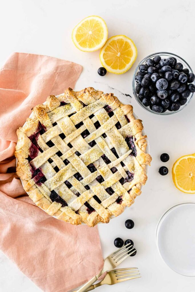 whole homemade blueberry pie with a lattice top layer of crust surrounded by white plates, blueberries and lemon slices