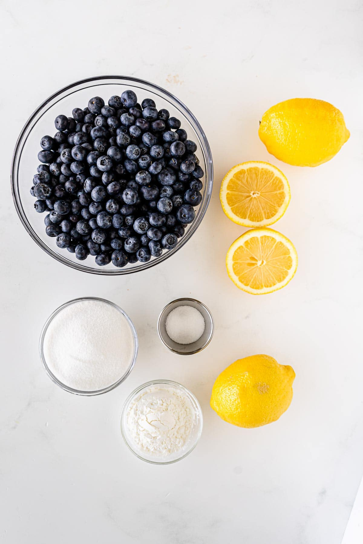 a bowl of blueberries, lemons, and bowls of corn starch and sugar