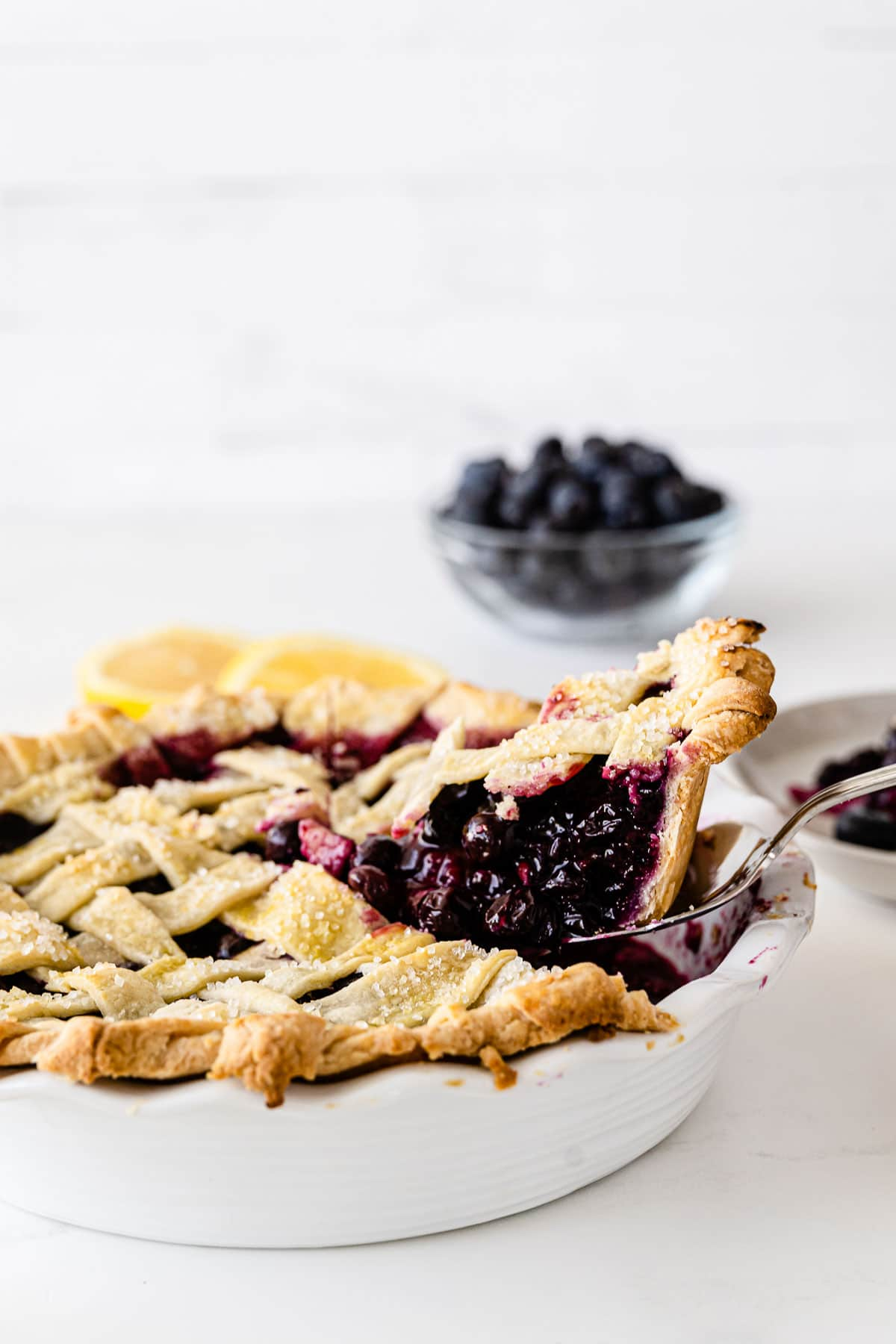 a slice of blueberry pie being taking out of a white pie plate