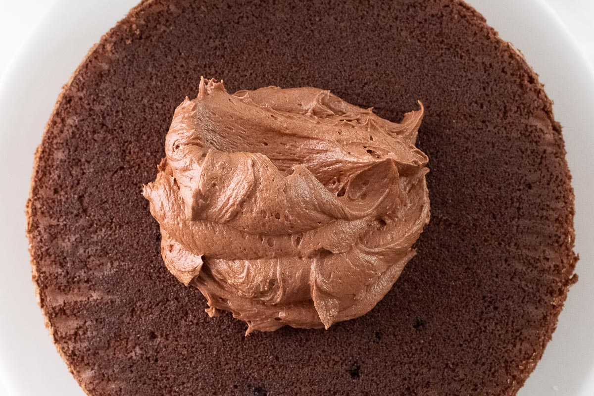 a mound of chocolate buttercream frosting on top of a round chocolate layer cake
