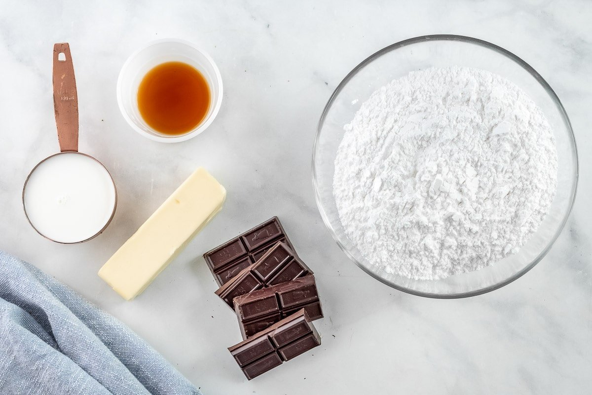 glass bowl of powdered sugar, four chocolate squares, stick of butter and two small bowls with milk and vanilla extract