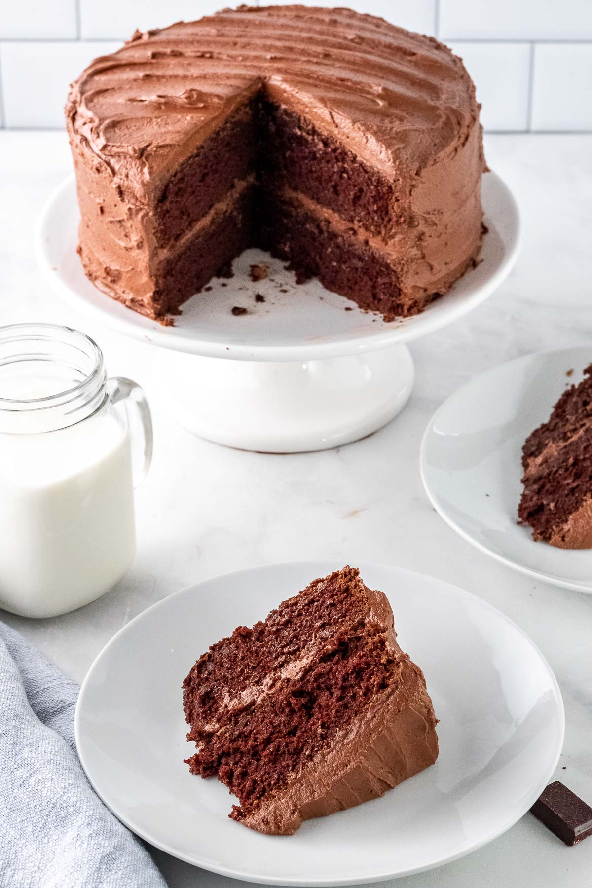 a slice of chocolate cake with chocolate frosting on a white plate with the whole cake on a cake stand in the background