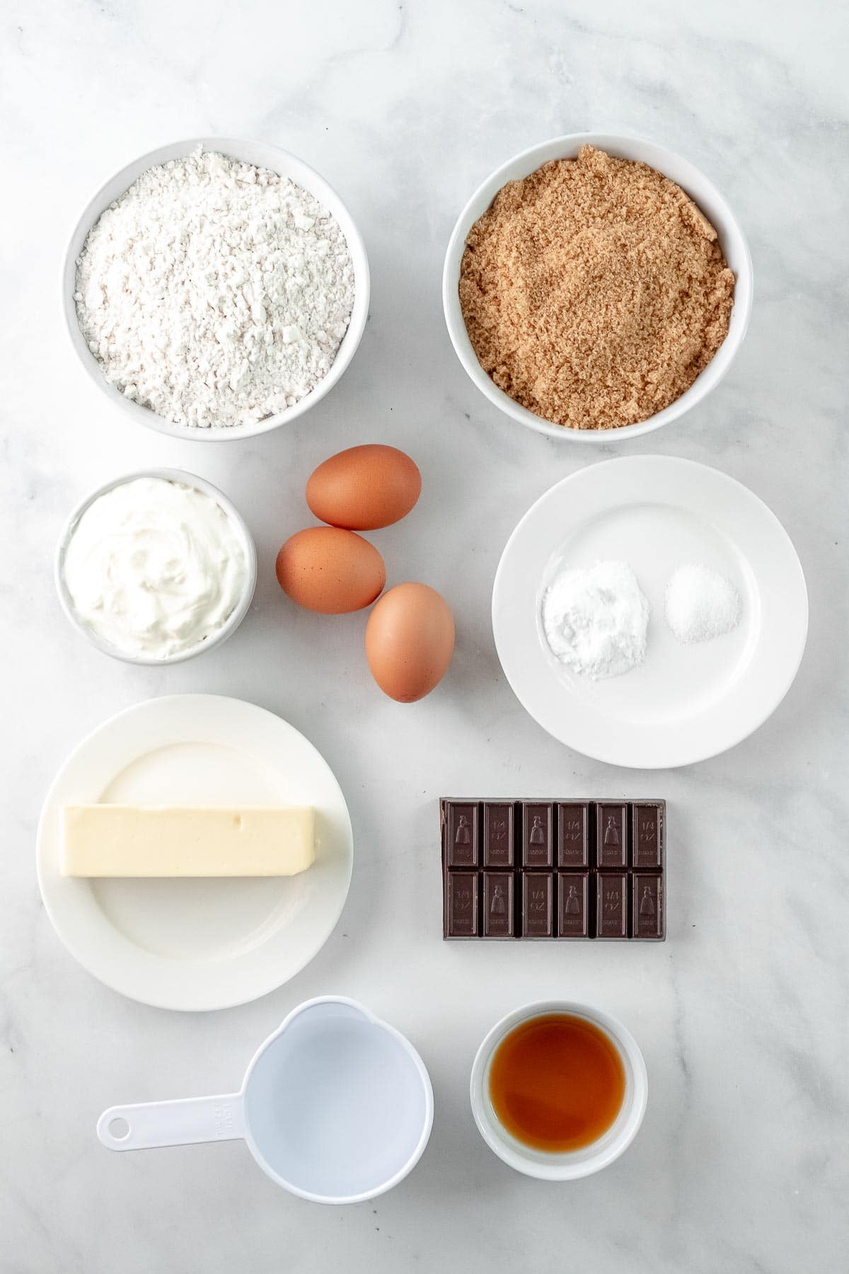 Ingredients for chocolate fudge cake in bowls on a white marble counter
