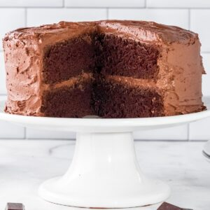 chocolate cake on a white can stand with a large section but out
