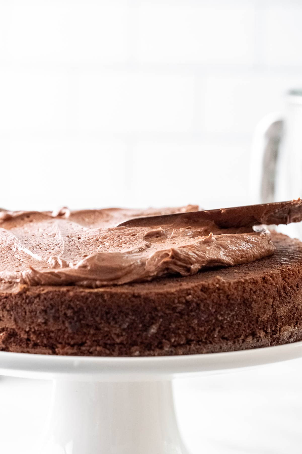chocolate frosting being spread onto a chocolate layer cake