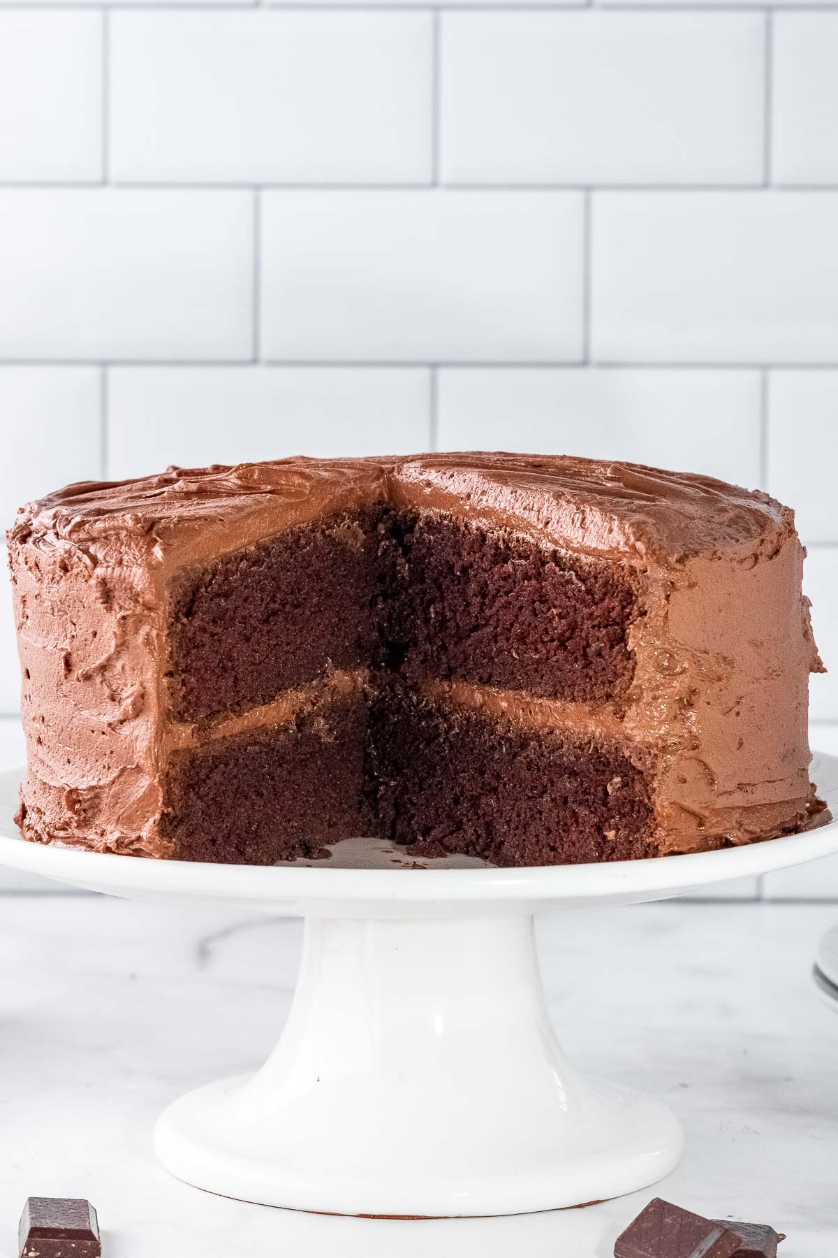 a white cake stand with a chocolate cake with chocolate frosting with a large piece cut out